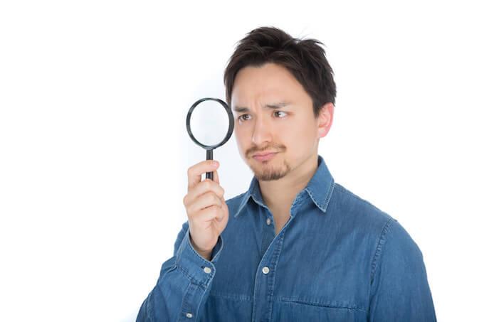 虫眼鏡を使う男性